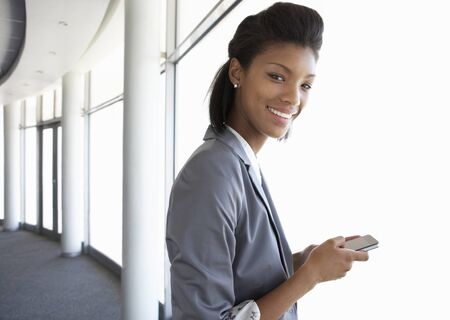 mobile phone: Young Businesswoman Standing In Corridor Of Modern Office Building Using Mobile Phone