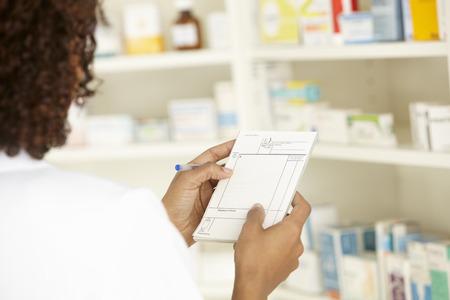 UK Female nurse in pharmacy with prescription Stock Photo