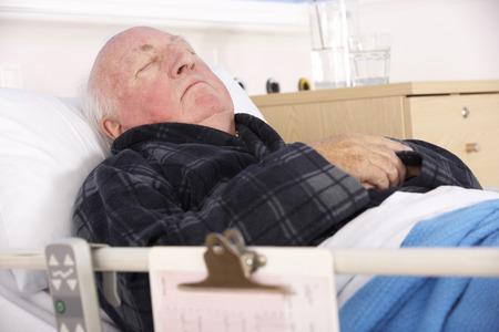 infirm: Senior man in hospital bed Stock Photo