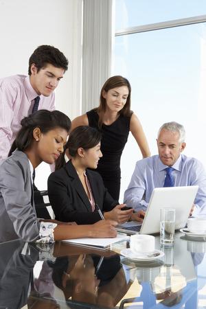 empleado de oficina: Grupo de hombres de negocios Tener Reunión Alrededor portátil en la mesa de cristal