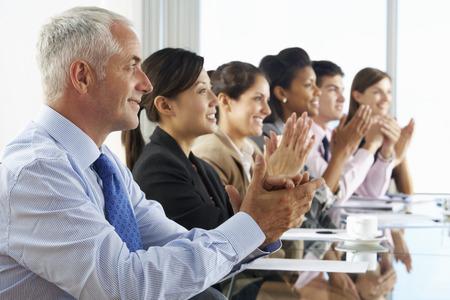 personas escuchando: Línea de hombres de negocios que escuchan la presentación asentados en el cristal Mesa de reuniones