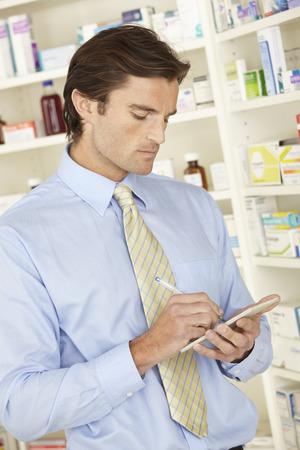 UK pharmacist in pharmacy with prescription