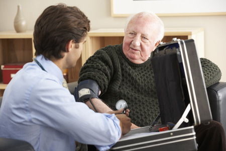 Doctor taking senior mans blood pressure at home