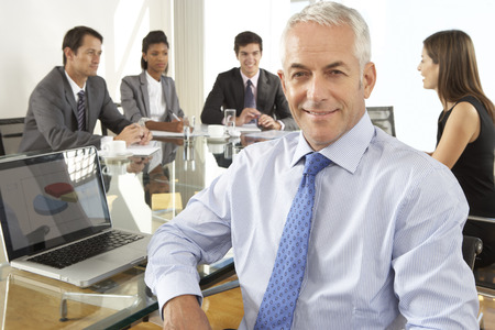 worker man: Businessman Sitting Around Boardroom Table With Colleagues