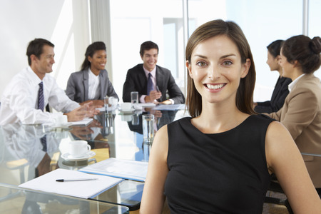 office meeting: Businesswoman Sitting Around Boardroom Table With Colleagues Stock Photo