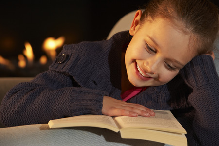 7 year old girl: Portrait 7 year old girl reading by firelight