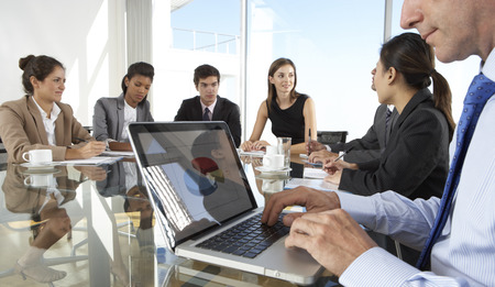 meeting table: Close Up Of Businessman Using Laptop During Board Meeting Around Glass Table