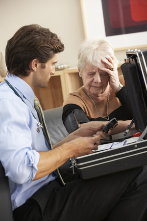house call: Doctor taking senior womans blood pressure at home