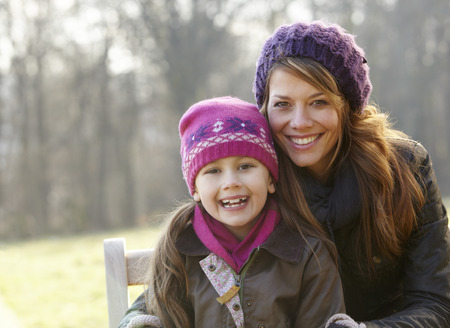 7 year old girl: Portrait mother and daughter outdoors in winter Stock Photo