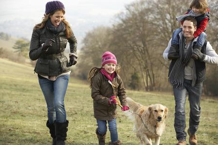 caminando: Familia y perro en el país a pie en invierno