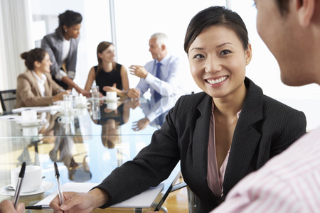 group of business people: Two People Having Meeting Around Glass Table In Boardroom With Colleagues In Background