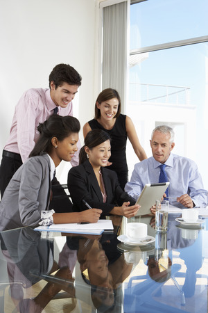 Group Of Business People Having Meeting Around Tablet Computer At Glass Table