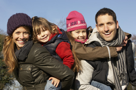 7 year old girl: Parents giving piggybacks to children on winter walk Stock Photo