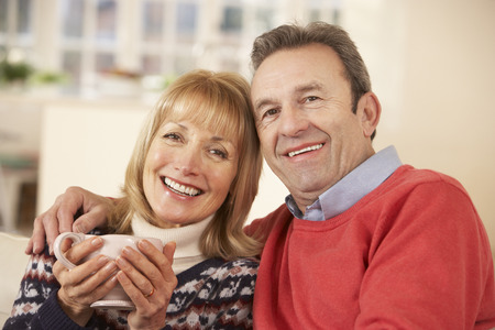 happily: Portrait mature couple relaxing at home