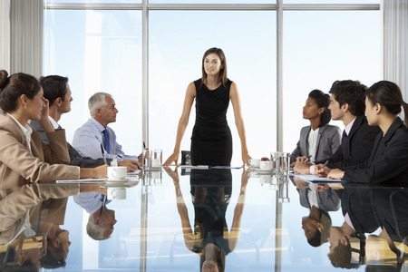 Group Of Business People Having Board Meeting Around Glass Table. Stock Photo