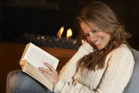 Donna lettura davanti al fuoco a casa