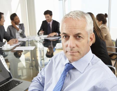 mixed age range: El hombre de negocios se sienta alrededor de la sala de reuni�n Mesa Con Los Colegas