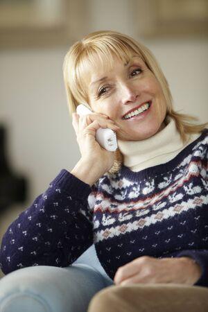 cordless: Senior woman talking on cordless phone at home