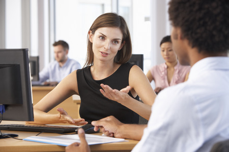 office worker: Two Business People Having Meeting In Busy Office
