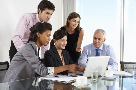 office meeting: Group Of Business People Having Meeting Around Laptop At Glass Table Stock Photo