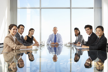 mixed age range: Group Of Business People Having Board Meeting Around Glass Table