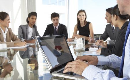 Cierre de negocios usando la computadora portátil Durante reunión de la Junta alrededor de la mesa de cristal Foto de archivo - 42163892