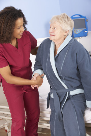 caring for: Nurse helping senior woman out of bed in hospital