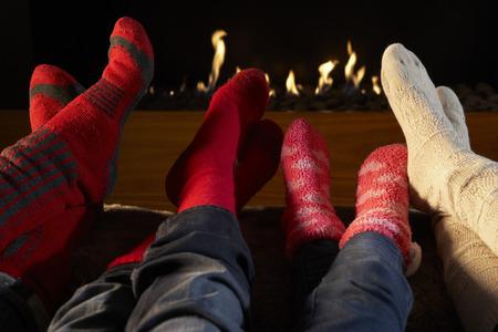 pies masculinos: Cuatro pares de pies en los calcetines que se calientan por el fuego