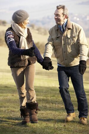 walk in: Mature couple on country walk in winter Stock Photo