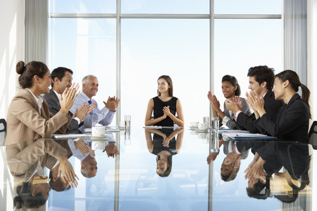 board room: Group Of Business People Having Board Meeting Around Glass Table