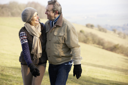 older couples: Mature couple on country walk in winter Stock Photo