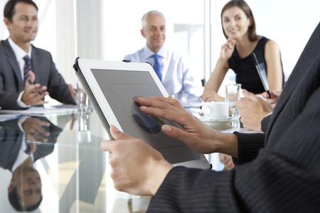 reunion de trabajo: Cerca De Empresaria Utilizando Tablet Computer Durante reuni�n de la Junta alrededor de la mesa de cristal