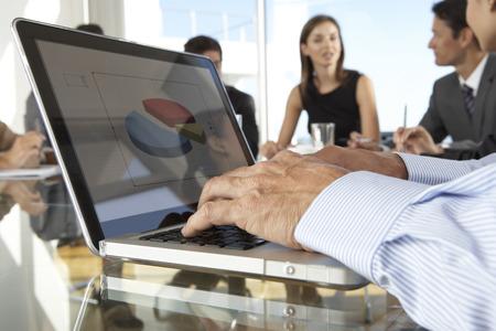 mixed age range: Cierre de negocios usando la computadora port�til Durante reuni�n de la Junta alrededor de la mesa de cristal