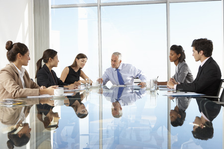ビジネス: ガラスのテーブルの周りの理事会を持つビジネス人々 のグループ