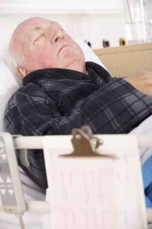 adult 80s: Senior man in hospital bed Stock Photo