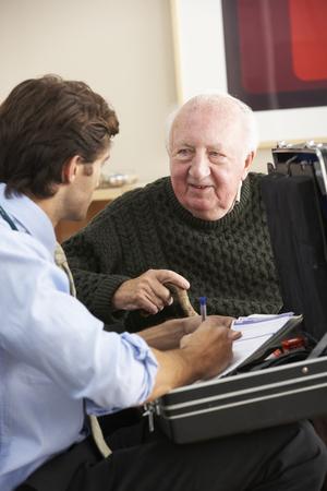 adult 80s: Doctor visiting senior man at home