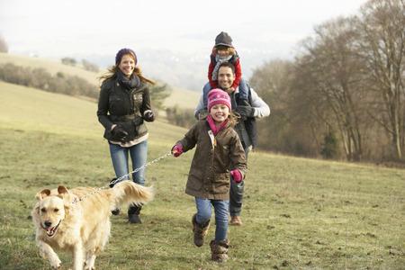 paisaje rural: Familia y perro en el país a pie en invierno