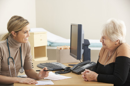 general practitioner: Senior woman visiting Doctor Stock Photo