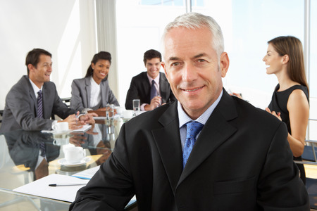 workers group: Businessman Sitting Around Boardroom Table With Colleagues
