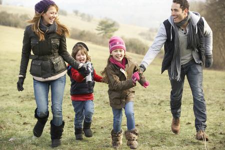 Familia que se divierte en el país en invierno Foto de archivo