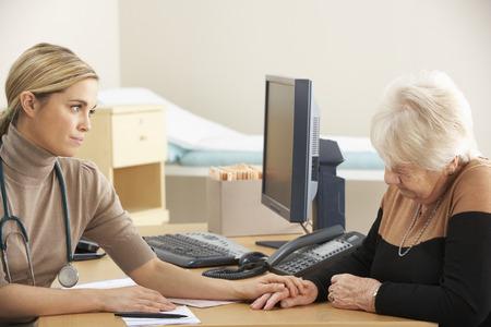 Arts geruststellend senior vrouw patiënt