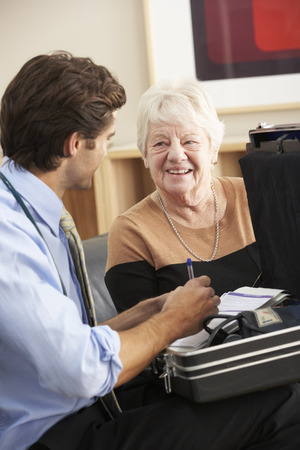 british man: Doctor visiting senior woman at home