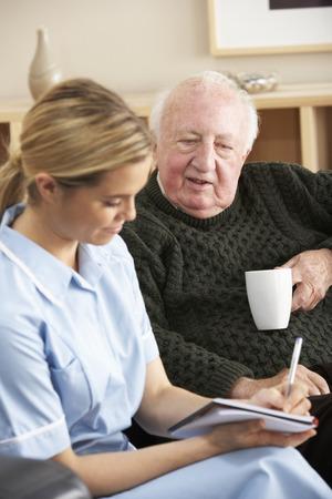 persona de la tercera edad: Enfermera visita hombre senior en casa