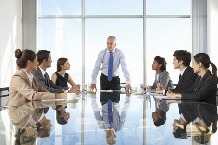 people in office: Group Of Business People Having Board Meeting Around Glass Table