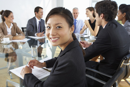 mixed age range: Asian Businesswoman Sitting Around Boardroom Table With Colleagues Stock Photo