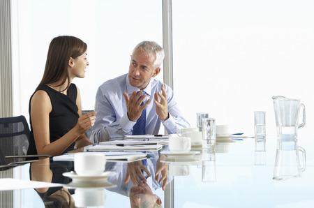 非公式な議論を持つ会議室のテーブルの周りに座っている 2 つのビジネス部門の同僚