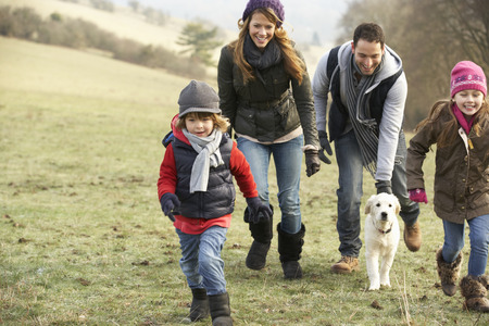 family with one child: Family and dog having fun in the country in winter Stock Photo