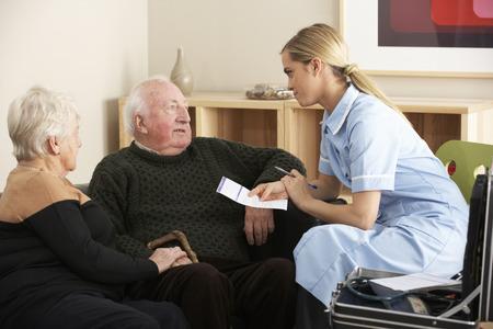 jubilados: Enfermera visita pareja de ancianos en el hogar Foto de archivo