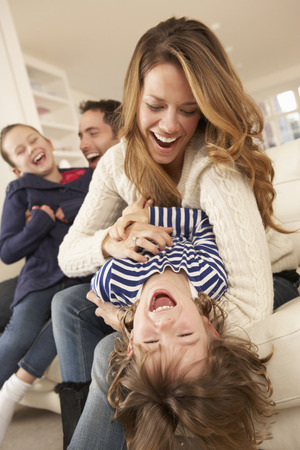 woman laughing: Parents playing with children at home Stock Photo