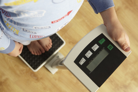 waist down: Young boy standing on digital scales cropped waist down Stock Photo